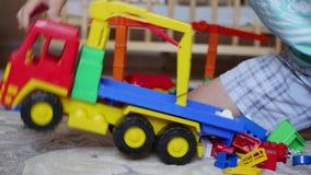 De kindspelen met het speelgoed in de speelkamer stock footage
