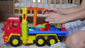 De kindspelen met het speelgoed in de speelkamer stock videobeelden