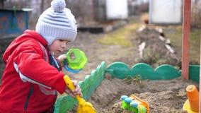 De kindspelen met het speelgoed in de zandbak De zonnige dag van de zomer Pret en spelen in openlucht stock footage