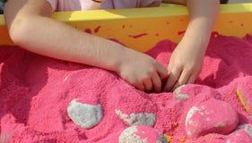 De kindspelen met van hem dient het roze zand in royalty-vrije stock fotografie