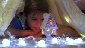 De kindspelen in de ruimte van de kinderen in een tent met een Kerstmislicht Gelukkige kinderjaren stock footage