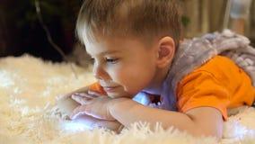 De kindspelen in de ruimte van de kinderen met een Kerstmislicht, ligt hij op een zachte deken en bouwt gezichten gelukkig stock videobeelden