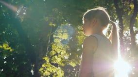 De kindtribunes in de straal, de zon glanst op haar gezicht Word verloren in een feebos stock videobeelden