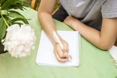 De kindzitting bij een lijst en houdt in handenpen voor hem Royalty-vrije Stock Afbeelding