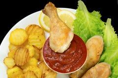 De kippenbenen dompelden in ketchup op een witte plaat met sla onder en roosterden aardappelsmening van hierboven geïsoleerd op z Royalty-vrije Stock Foto's