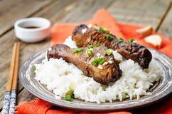 De kippenbenen van het soja balsemieke knoflook met rijst stock afbeeldingen