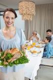 De kippenbraadstuk van de vrouwenholding met familie bij eettafel Royalty-vrije Stock Foto's