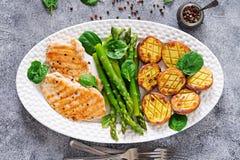 De kippenfilet op een grill met wordt gekookt versiert van asperge en aardappelen in de schil die royalty-vrije stock afbeelding