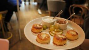 De klaar kaaspannekoeken op platen met plakken van peer en druiven met zure room en de honing in pialochki, de kelner houden stock footage