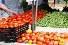 De klant bereikt voor Tomaat bij de Markt van Landbouwers Stock Afbeeldingen