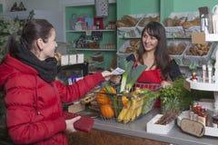 De klant betaalt contant geld bij de kassa van een hoekwinkel Stock Foto's