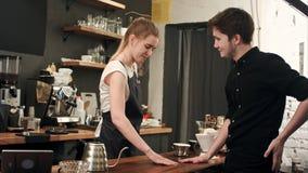 De klant bij koffiewinkel betaalt glimlachende serveerster met contant gelddollar Royalty-vrije Stock Foto's