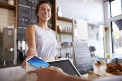 De klant bij koffiewinkel betaalt glimlachende serveerster met kaart stock fotografie