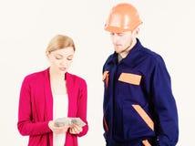 De klant geeft geld aan hersteller, bouwer, werktuigkundige met toolbox stock afbeeldingen