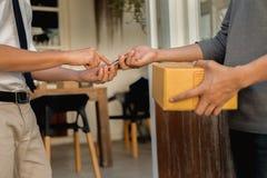 De klant overhandigt het toevoegen handtekening in mobiele telefoon, mens die pakketpostdoos van koerier met de mens van de lever royalty-vrije stock foto's