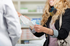De Klant van apothekerreceiving money from voor Geneesmiddelen Stock Fotografie