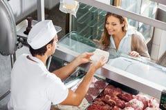De Klant van slagersshowing meat to bij Slachterij stock afbeelding