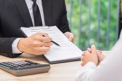 De klant of de vrouw neemt een besluit om een contract te ondertekenen wanneer busine stock foto