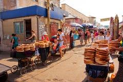 De klanten van Centrale Aziatische markt kopen traditioneel brood openlucht Stock Afbeeldingen
