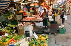 De klanten van openluchtmarkt kiezen zeevruchten, vruchten en groenten op bezige smalle straat Royalty-vrije Stock Afbeeldingen