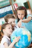 De klasgenoten helpen aan elkaar om iets te vinden Stock Afbeelding