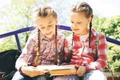 De klasgenoten zitten en lezen een boek stock afbeelding