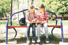 De klasgenoten zitten en lezen een boek stock foto