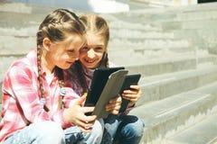 De klasgenoten zitten met de tabletten stock foto's