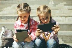 De klasgenoten zitten met de tabletten stock afbeeldingen