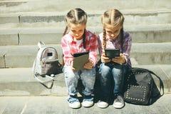 De klasgenoten zitten met de tabletten royalty-vrije stock afbeelding