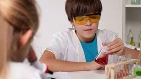 De klasse van de basisschoolchemie - jonge geitjes het experimenteren stock footage