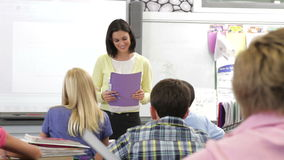 De Klasse van leraarshelping pupils in stock videobeelden