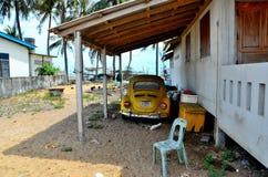 De klassieke Duitse gele die auto van Volkswagen Beetle onder schuilplaats in Pattani Thailand wordt geparkeerd royalty-vrije stock afbeeldingen