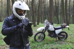 De klassieke enduromotorfiets van weg in de lentebos, mens in een modieus leerjasje gebruikt een smartphone, Motorrijdertoestel,  royalty-vrije stock foto's