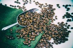 De klassieke oude achtergrond van het filmontwerp van de geroosterde koffiebonen op roestvrije lepel en gezet rond groene hennepd royalty-vrije stock foto's