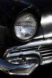 De klassieke oude voorkoplamp en de grill van de jaren '60 zwarte auto royalty-vrije stock foto