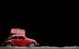 De klassieke rode auto die de Kerstman deliverling stelt in sneeuwweath voor Stock Foto
