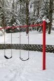 De klassieke schommeling plaatste in een openbaar park, een rode steuntribune en zwarte rubberschommelingszetels, sneeuwdag royalty-vrije stock fotografie
