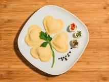 De klaver maakte met gevormd hart vier, eigengemaakte ravioli en enkelen weinig uit elkaar geplaatste kaas Stock Foto's