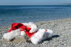 De kleding en de hoed van Santa Claus liggen op een grote steen op de kust De kerstman ging zwemmend stock fotografie
