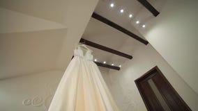 De kleding van de bruid hangt onder het plafond Zeer mooi en elegant Huwelijk stock video