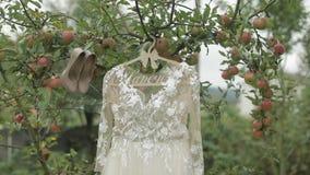 De kleding van de bruid hangt op een appelboom Zeer mooi en elegant Huwelijk stock video