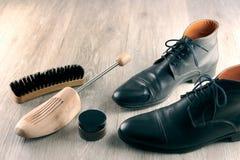 De kledingslaarzen van zwarte leermensen en de hulpmiddelen van de schoenzorg stock afbeelding