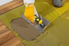 De kleefstof van de tegel op houten vloer Royalty-vrije Stock Foto's