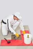 De Kleefstof van de Tegel van de arbeider met de Vloer van de Tegel van de Troffel Stock Fotografie