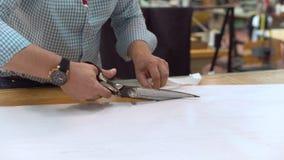 De kleermaker die het duidelijke patroon op stof met grote schaar op de werkbank in zijn winkel verwijderen, sluit omhoog mening  stock footage