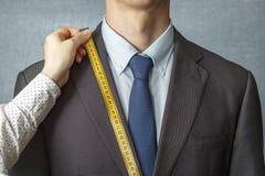 De kleermaker meet het kostuum met een het meten bandclose-up stock afbeeldingen