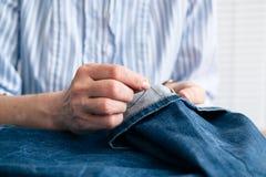 De kleermaker naait de boord van jeans in workshop royalty-vrije stock foto's