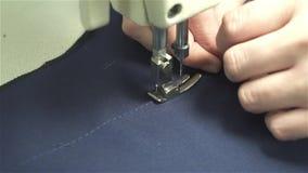 De kleermaker naait kleren op een naaimachine van blauwe stof stock videobeelden