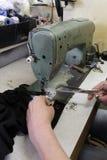 De kleermaker naait kleren in uitstekende workshop in Sofia, Bulgarije - september 9, 2015 De mensen naaien kleren Het herstellen Royalty-vrije Stock Afbeelding
